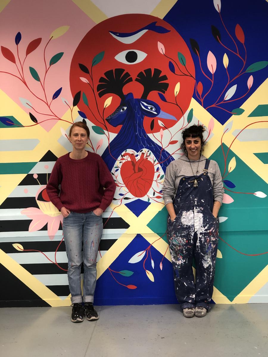 Portrait des artistes Jennifer Hugot et Alexandra-Isis Petracchi devant la fresque