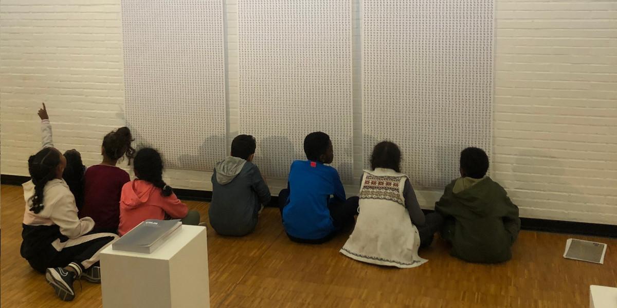 Groupe scolaire en visite guidée, contemplant « Bibliothèque d'images de Babel » (2017), une impression générée par ordinateur